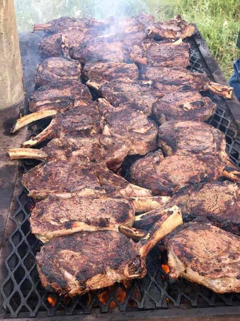 Cowboy steaks being cooked over an open fire.