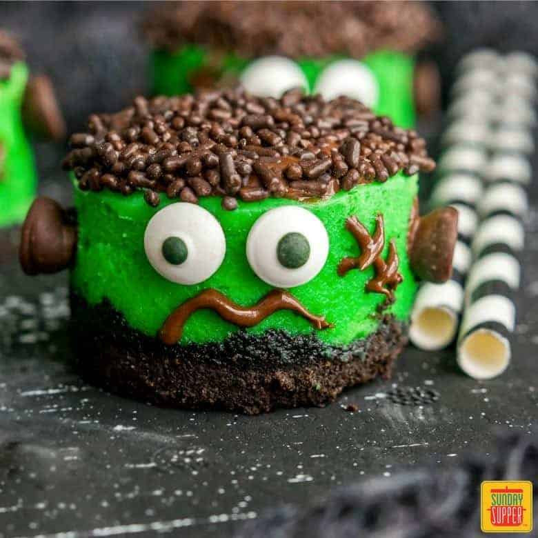Mini Halloween Cheesecakes decorated like Frankenstein on a black surface