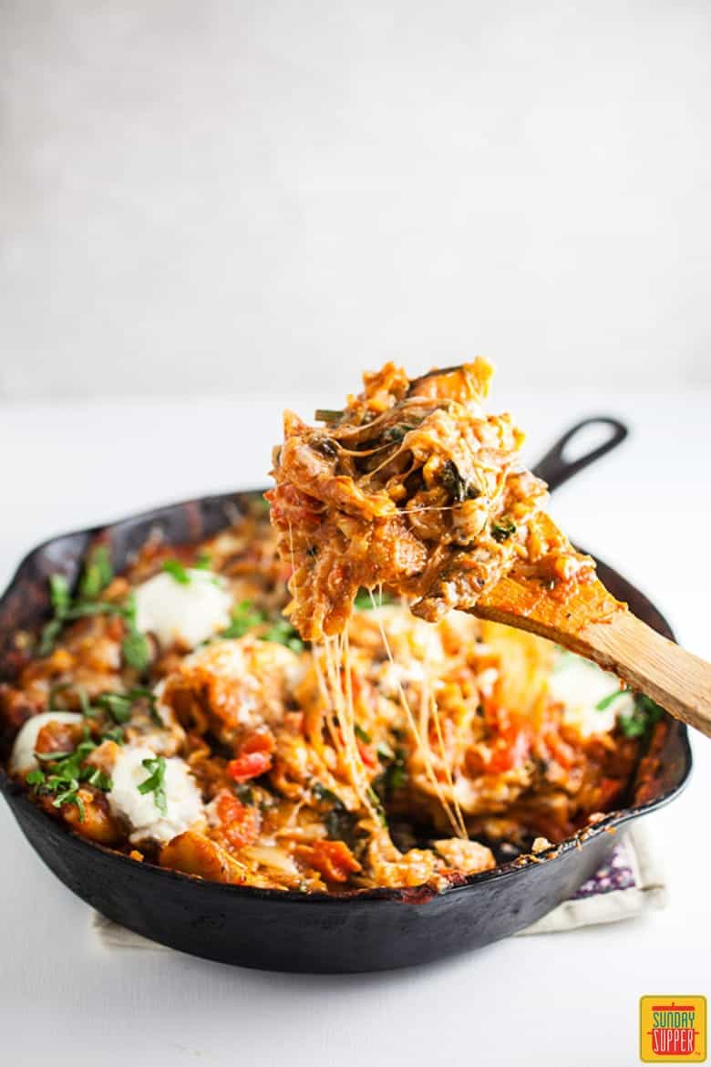 Cast Iron Skillet Lasagna being served from the skillet with a wooden spoon