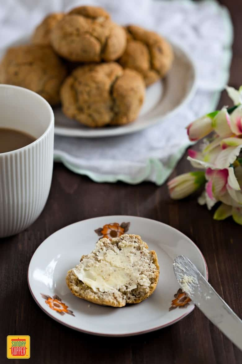 Gluten Free Rolls on a table with coffee and flowers. A slice of bread roll on a plate, covered with butter