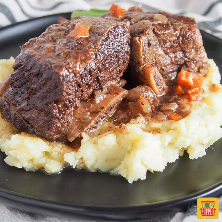 slow cooker short ribs on a bed of mashed potatoes served on a black plate