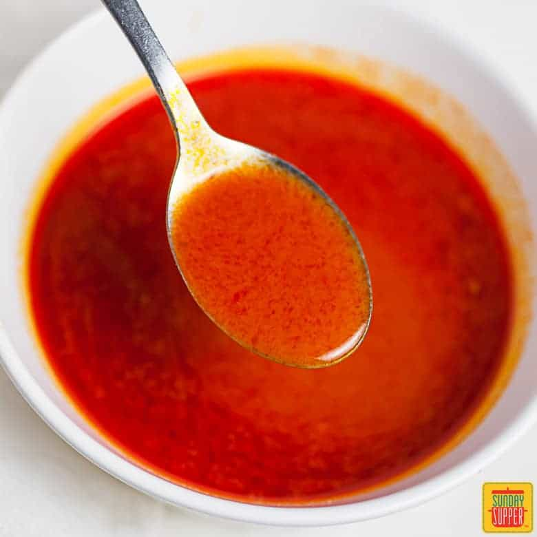 How to Make Buffalo Sauce: Buffalo sauce on spoon after being mixed