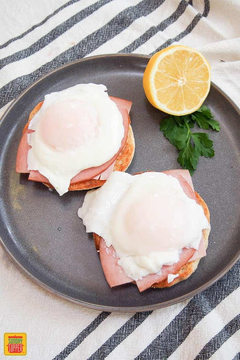 How to Make Eggs Benedict: putting together eggs benedict just before pouring on hollandaise sauce