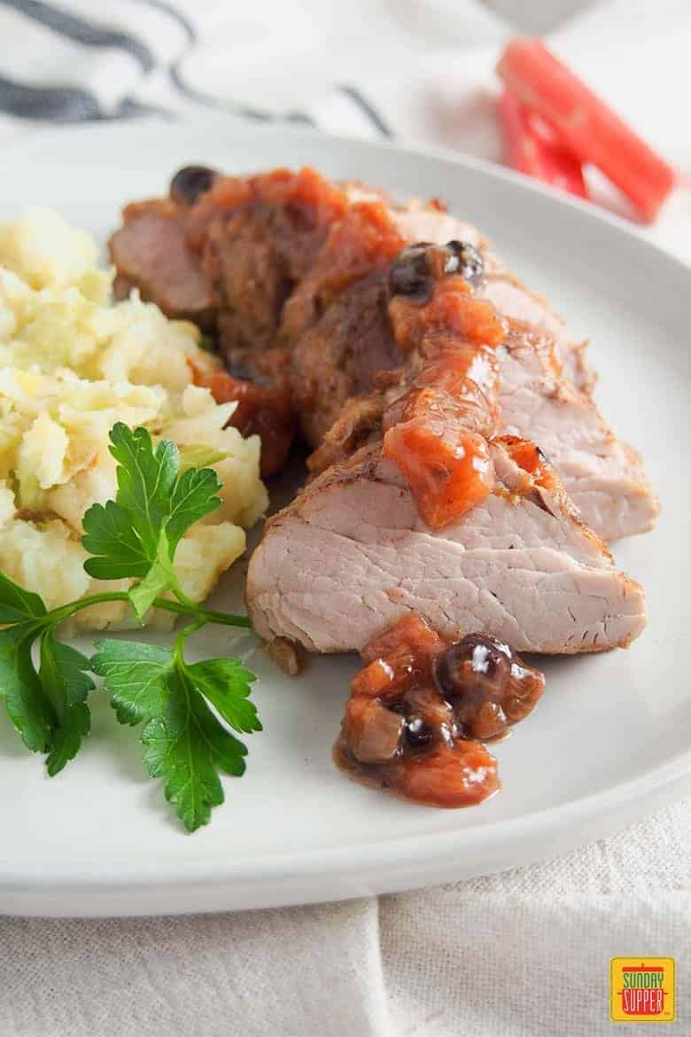 Pork tenderloin with rhubarb chutney served on a white plate with colcannon