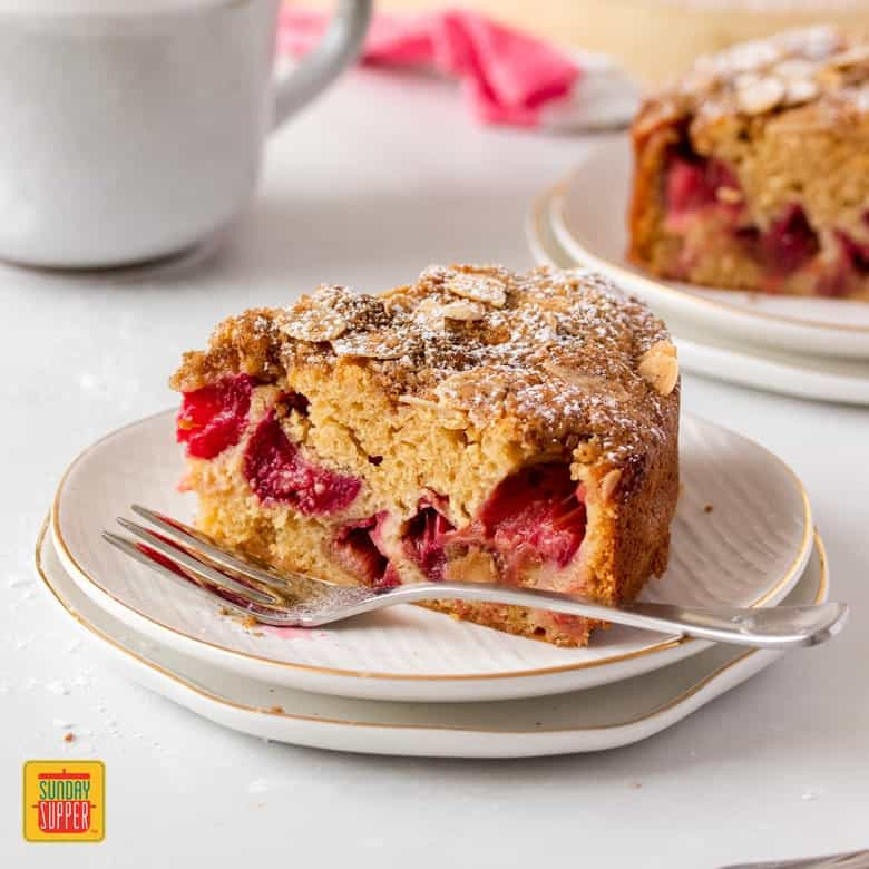A slice of rhubarb cake on a plate with a fork next to it and mug in the background