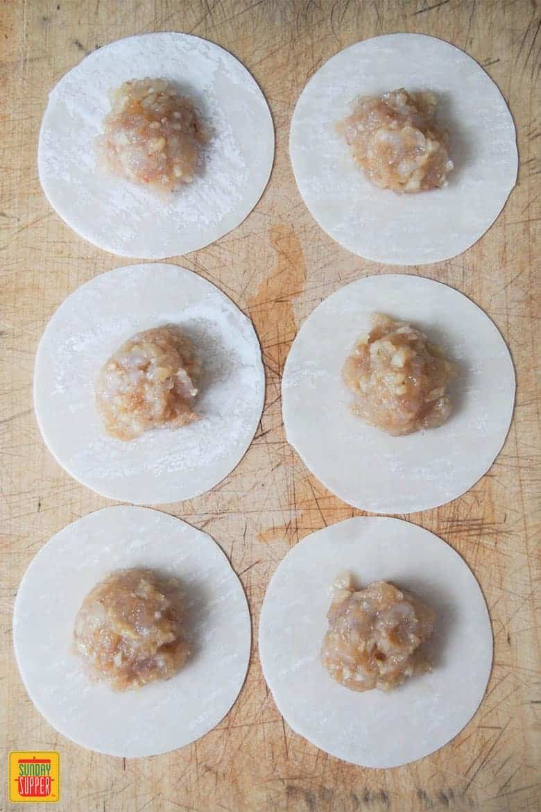 putting filling for shrimp shumai in dumpling wrappers