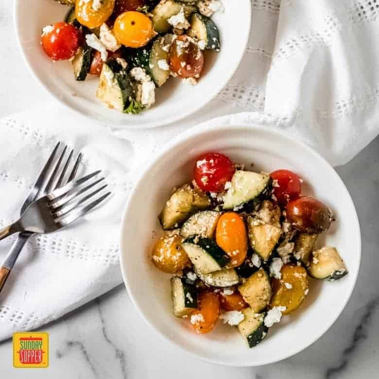 two small white bowls with tomato cucumber feta salad
