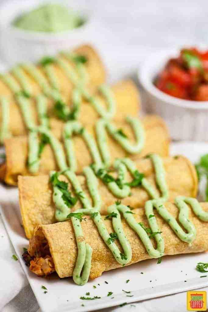 Chicken Taquitos Recipe: chicken taquitos on white platter with fresh avocado crema