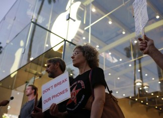 Woman stands outside apple store and carrys protesting sign