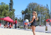 Student athlete stands on sand during volleyball match
