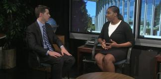 A man and woman sit facing one another during interview