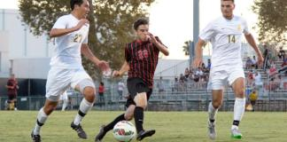 CSUN player races opposing team for control of the ball