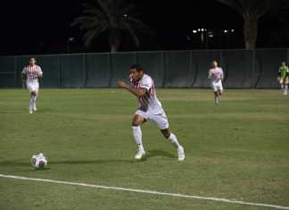 Soccer player chases ball down field