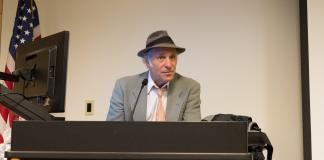 Greg Palast speaks at the podium