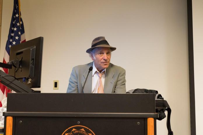 Greg Palast speaks at the podium