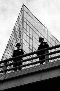 Two police officers shown standing on a bridge