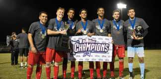 "Seven men are posing with medals, trophies, and a sign which says, ""Big West Champions"""