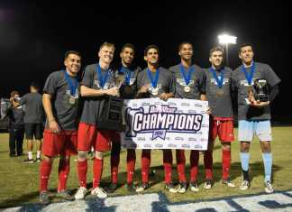 """Seven men are posing with medals, trophies, and a sign which says, """"Big West Champions"""""""