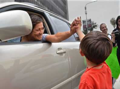 Woman in car holds hands with small child