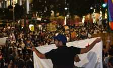 One protester holds up the California Flag surrounded by many other fellow protesters