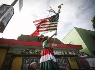 Woman waves an American flag and a Mexican flag