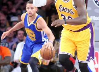 Basketball players run across the court