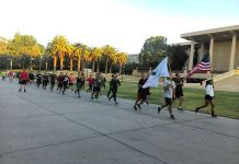 CSUN students pictured running in front of the Oviatt Library waving flags