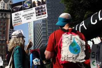"""Protestors pictured in Downtown LA, man hold backpack that says, """"I stand with standing rock"""""""