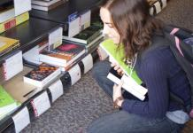 Woman pictured in bookstore browsing the textbooks