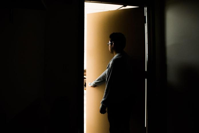 Man pictured in a dark room opening a door into a lit room
