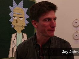 Still shows Jay Johnson being interviewed at the LA art gallery