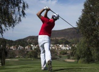 Golf player takes a swing at the ball
