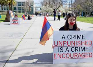 """Student holds sign that reads,""""A crime unpunished is a crime encouraged"""""""