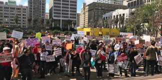 Protesters wave their picket signs at Pershing Square