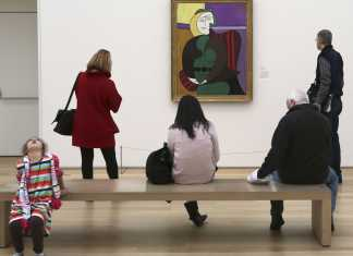 "Several people stand in front of picasso's ""red armchair"" painting which appears to be an abstract image of a woman sitting in a chair"