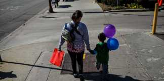 mother and son walk down the street together