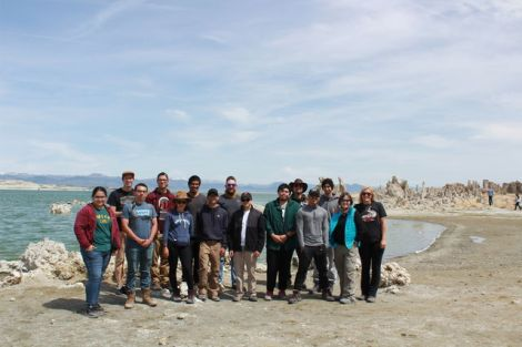 a small group of Geomorphology students pose for a photo next to a lake