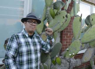 man pictured posing next to a cactus wearing a green flannel tshirt and a fedora hat