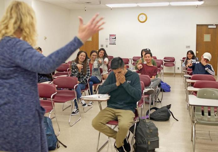 Photo shows a class demonstration of public shaming, while the teacher and the class jokingly tease one student he pretends to cry