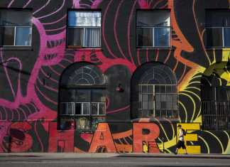 "Man walks past building covered in a rainbow mural that says, ""share"" and features an abstract design"