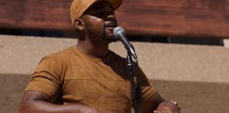 Caleb Word is performing spoken word poetry for Poetry Palooza wearing a matching light brown suede hat and shirt
