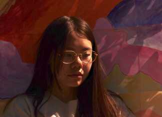 Trina, a young woman with black hair and glasses sits in front of a colorful abstract painting