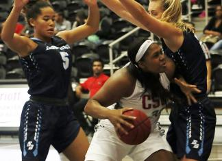 CSUN athlete tries to dribble her way towards the basket past the two girls blocking her