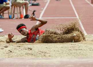 Man pictured sliding through the dirt after completing his long jump