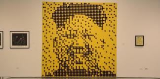 Photo of an art piece in CSUN gallery shows a portrait of Kim Jong Un made on a yellow canvas using brown cones