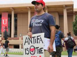 """Man pictured on the Oviatt lawn wearing a shirt that says, """"Hillary for Prison"""" he is holding a sign up that says, """"Antifa is the new facism"""""""