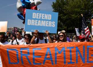 "protesters hold up several signs, on of them which reads, ""dreaming"" and another says, ""defend dreamers"""