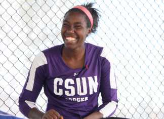 girl in purple shirt reading CSUN SOCCER and pink headband