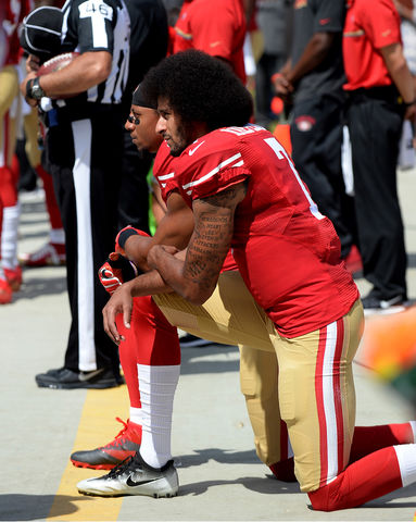 professional football player in red and gold uniform kneeling
