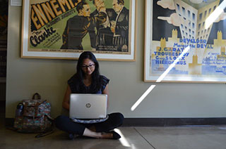 girl sitting on floor with laptop above her a movie poster